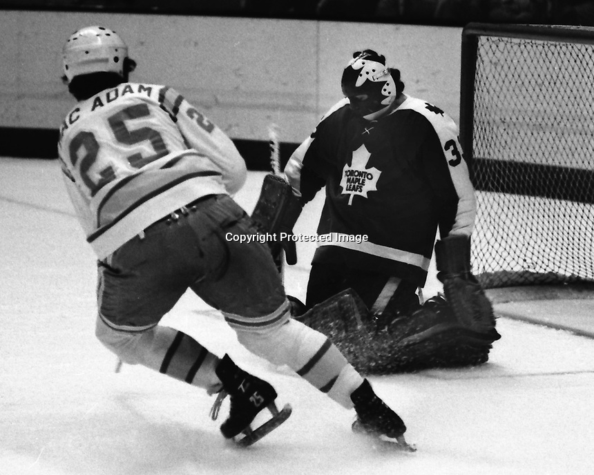 Seals Al MacAdam shoots on Toronto Maple Leafs goalie Doug Favell (1975 photo/Ron Riesterer)