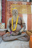 Sadhu Baba, follower of Shiva, meditates in the morning outside the Shiva temple on the stairways to river Ganga