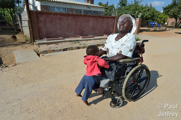 Edith Ncube had polio as a child and today uses a wheelchair in Bulawayo, Zimbabwe, where she lifts a neighbor child into her lap. Her wheelchair was provided by the Jairos Jiri Association with support from CBM-US.