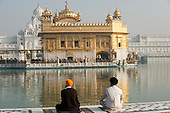 Amritsar, Punjab, India.  The Golden Temple - Harmandir Sahib - with two Sikh men sitting cross-legged beside the holy water of the Amrit Sarovar lake, looking at the Harmandir Sahib temple.