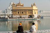 Amritsar, Punjab, India.  The Golden Temple - Harmandir Sahib - with two Sikh men sitting cross-legged beside the holy water of the Amrit Sarovar lake, looking at the Harmandir Sahib temple.