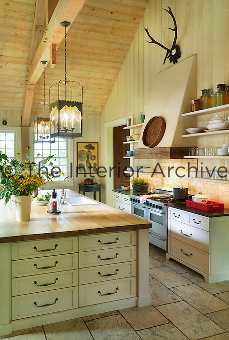 The large country kitchen has a double-height ceiling and a pair of lanterns hanging from the rafter above the sink