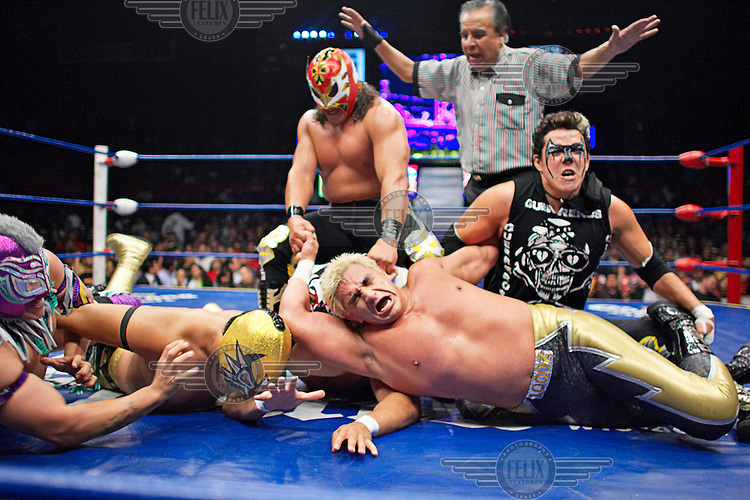 Luchadores (fighters) involved in a six person melee. Lucha Libre is a style of wrestling started in Mexico in 1933. The name means Free Fight, and matches tend to be focussed on spectacle and theatre with fans cheering for their favourite characters, who wear masks while jumping from the ropes, flipping opponents, and occasionally crashing into the crowd..©Jacob Silberberg/Panos/Felix Features.