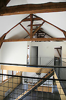A series of large wooden A-frames runs the length of the barn to support the roof while underneath a series of partitions divides the space into bedrooms