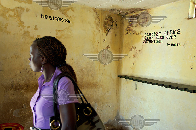 Baindu Koroma, a paralegal who works for Timap for Justice, inside the custody office at Bo central police station where dual notices printed on the damp affected and faded yellow walls read 'NO SMOKING' and 'CUSTODY OFFICE. PLEASE AVOID OVER DETENTION. BY ORDER.'<br /> Koroma's work includes making regular visits to police stations, the prison, and the courts to monitor whether people are being afforded their lawful rights, for example, the right to bail, legal representation, detention without charge, etc, and if not to advocate on their behalf.