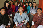 A Bhutanese woman manager, owner and her business team. Many of the Bhutan's businesses and owned and run by women. Thimpu, Bhutan..Bhutan the country that prides itself on the development of 'Gross National Happiness' rather than GNP. This attitude pervades education, government, proclamations by royalty and politicians alike, and in the daily life of Bhutanese people. Strong adherence and respect for a royal family and Buddhism, mean the people generally follow what they are told and taught. There are of course contradictions between the modern and tradional world more often seen in urban rather than rural contexts. Phallic images of huge penises adorn the traditional homes, surrounded by animal spirits; Gross National Penis. Slow development, and fending off the modern world, television only introduced ten years ago, the lack of intrusive tourism, as tourists need to pay a daily minimum entry of $250, ecotourism for the rich, leaves a relatively unworldly populace, but with very high literacy, good health service and payments to peasants to not kill wild animals, or misuse forest, enables sustainable development and protects the country's natural heritage. Whilst various hydro-electric schemes, cash crops including apples, pull in import revenue, and Bhutan is helped with aid from the international community. Its population is only a meagre 700,000. Indian and Nepalese workers carry out the menial road and construction work.