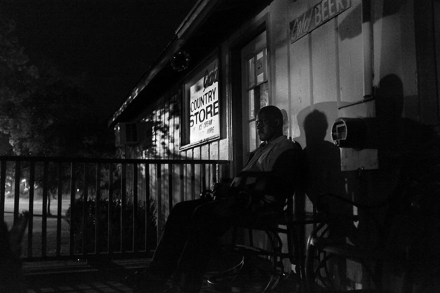 A member of the Hog Hammock community sits on the porch of the Graball Country Store, the only store on Sapelo Island.