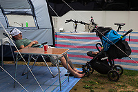 Switzerland. Canton Ticino. Tenero. Camping Campofelice. A swiss german father takes a nap in front of his caravan while his child sleeps in the stroller. A caravan, travel trailer, camper or camper trailer is towed behind a road vehicle to provide a place to sleep which is more comfortable and protected than a tent. It provides the means for people to have their own home on a journey or a vacation. Campers are restricted to designated sites for which fees are payable. 21.07.2018 © 2018 Didier Ruef