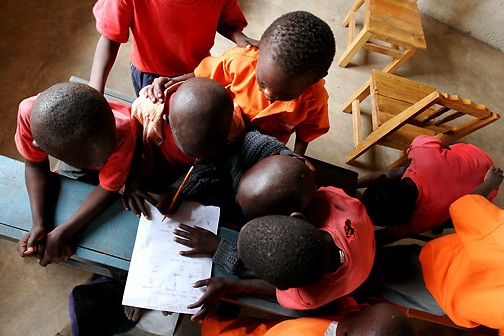 """Antony Kimathi is crowed by fellow students shouting, """"Finish"""" during a final exam at the Early Childhood Development school at Pepo La Tumaini Jangwani, a community based HIV/AIDS program in Isiolo, Kenya., on Tuesday, July  29, 2008.  (Photo by Bryce Yukio Adolphson, © 2008)"""