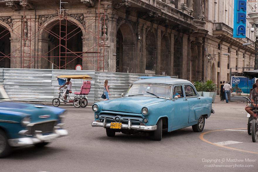 Havana, Cuba; a classic blue 1954 Ford drives down the Paseo de Marti in Havana