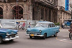 Havana, Cuba; a classic blue 1954 Ford drives down the Paseo de Marti in Havana