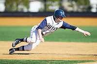 Ryan Busch (1) of the Georgetown Hoyas dives back towards first base against the Marshall Thundering Herd at Wake Forest Baseball Park on February 15, 2014 in Winston-Salem, North Carolina.  The Thundering Herd defeated the Hoyas 5-1.  (Brian Westerholt/Four Seam Images)