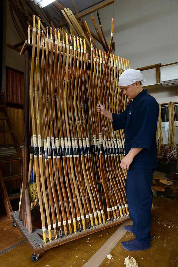 Keitarou Yokoyama holding a bow. Yokoyama Reimei Bowmakers, Miyakonojo, Miyazaki Prefecture, Japan, December 23, 2016. A handful of bowyers from the Kyushu city of Miyakonojo make over 90% of all the bows used in traditional Japanese archery. The bows are made from laminated bamboo and haze wood in process that consists of over 200 individual tasks. At over two meters from tip to tip the bows the longest used in the world.