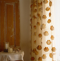 Scallop shells have been used to decorative effect sewn to the curtains of this rustic bedroom