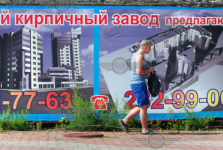 A man walks past big posters advertising new real estate development in the city centre of Krasnoyarsk.