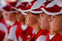 A team of young baseball players sit in the dugout as they watch their team.