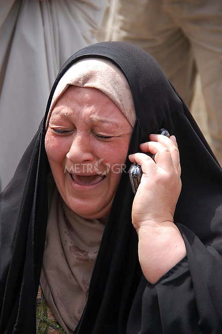 BAGHDAD, IRAQ: A woman is on call to find out about her daughter who works in a bank across the  Iranian Embassy after car bombs go off in Baghdad...Three car bombs hit the centre of the Iraqi capital, Baghdad, in quick succession, killing at least 30 people and injuring about 160 people.  The bombs appeared to target the Iranian embassy, and the Egyptian, Syrian and German missions in Iraq.