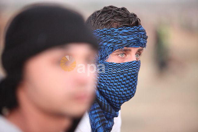 A masked Palestinian protester looks on during clashes with Israeli troops near a border fence between Israel and the Gaza Strip on October 14, 2015 east of Bureij in central Gaza. The outbreak of violence between Palestinians and Israeli forces in recent weeks has worsened in October, raising fears of a third intifada, or uprising. Photo by Ashraf Amra