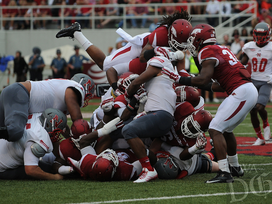 STAFF PHOTO ANTHONY REYES • @NWATONYR<br /> Alan Turner Razorbacks safety jumps into a pile stopping a run of Nicholls State in the second quarter Saturday, Sept. 6, 2014 at Razorback Stadium in Fayetteville.