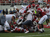 STAFF PHOTO ANTHONY REYES &bull; @NWATONYR<br /> Alan Turner Razorbacks safety jumps into a pile stopping a run of Nicholls State in the second quarter Saturday, Sept. 6, 2014 at Razorback Stadium in Fayetteville.