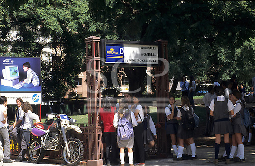 Buenos Aires, Argentina. Street scene; school students outside metro underground station with IT advert and motorbike.