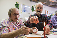 NWA Democrat-Gazette/BEN GOFF @NWABENGOFF<br /> Kent Kerr of Gravette shows Margaret Hellstern of Gentry how to melt wax to decorate her egg Friday, March 22, 2019, during a Ukrainian Easter egg decorating class at the Gentry Senior Activity Center. Kerr, with wife Joyce Kerr, lead the class on decorating eggs using wax to make designs and dips into multiple colors of dye to create eleborate designs. The senior activity center holds a craft making class each Friday.
