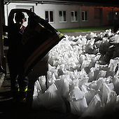 DOBRZYKOW, POLAND, MAY 23, 2010:.Rescue worker near the sand bags late at night..The latest chapter of disastrous floods in Poland has been opened today, May 23, 2010, after Vistula river broke its banks and flooded over 25 villages causing evacualtion of most inhabitants..Photo by Piotr Malecki / Napo Images..DOBRZYKOW, POLSKA, 23/05/2010:.Strazak pozna noca zaklada kurtke. Najnowszy akt straszliwych tegorocznych powodzi zostal rozpoczety dzis gdy Wisla przerwala waly na wysokosci wsi Swiniary kolo Plocka..Fot: Piotr Malecki / Napo Images ..