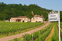 The vineyards, winery and chateau, and a white sign of Chateau Lassegue Saint Emilion Bordeaux Gironde Aquitaine France