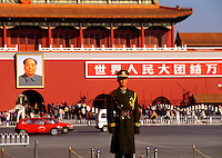 A Chinese policeman stands at attention outside of the walls of the Forbidden City; writing and a portrait of Chairman Mao Tse Tung in the background. Beijing, China.