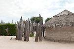 The Ovambo people in the rural North of Namibia still live in traditional homesteads, with some modern elements like brick or metal sheet huts and plastic chairs.
