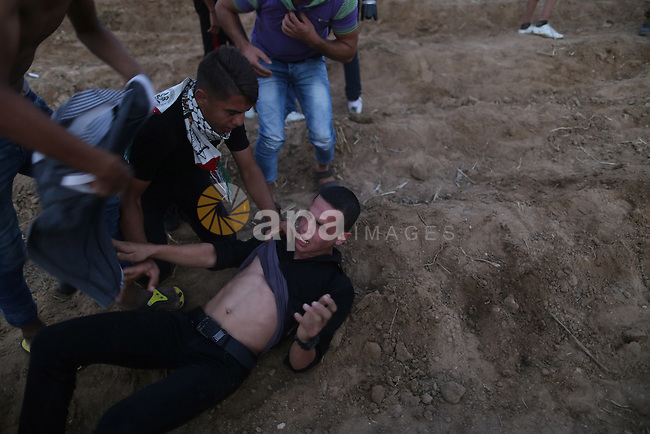"Palestinian protesters carry a comrade who was injured after tearing down a section of a border fence between Israel and the Gaza Strip during clashes with Israeli security forces on October 12, 2015, east of Bureij in central Gaza. Palestinian foreign minister Riad al-Malki accused Israel of seeking to spark ""a third intifada"", as violence again flared in Jerusalem, the West Bank and the Gaza Strip. Photo by Yasser Qudih"