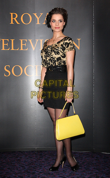 CHARLOTTE RILEY.Royal Television Society Programme Awards held at the Grosvenor House Hotel, Park Lane, London, England..March 16th, 2010.RTS full length black skirt beige pattern top yellow handbag purse floral print .CAP/ROS.©Steve Ross/Capital Pictures.