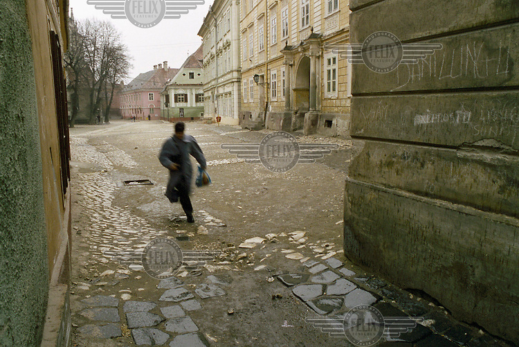 Man running through a square next to the old German saxon school in the town...