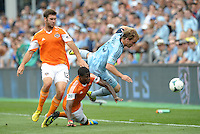 Seth Sinovic (15) defender Sporting KC goes over Kofi Sarkodie (8) defender Houston Dynamo, watched by Will Bruin..Sporting Kansas City and Houston Dynamo played to a 1-1 tie at Sporting Park, Kansas City, Kansas.