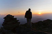 A hiker on the Appalachian Trail at sunset, near Mount Clay, in the White Mountains of New Hampshire.