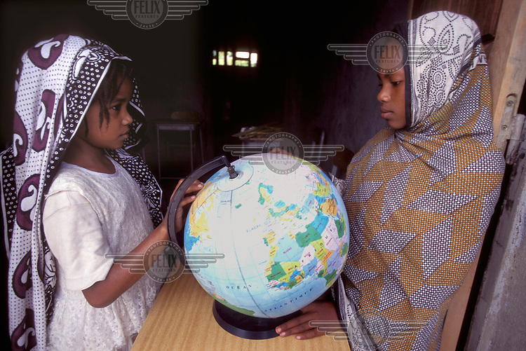 © Giacomo Pirozzi / Panos Pictures..COMOROS..School girls looking at a globe.