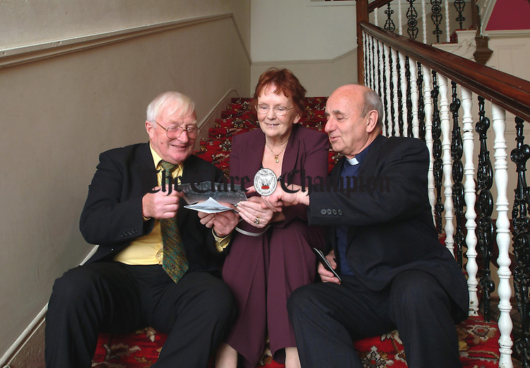 Jimmy and Ann Barrett and Mons. John Drury look back at some old photographs at St.Flannans College on Friday night last. Photograph by John Kelly.