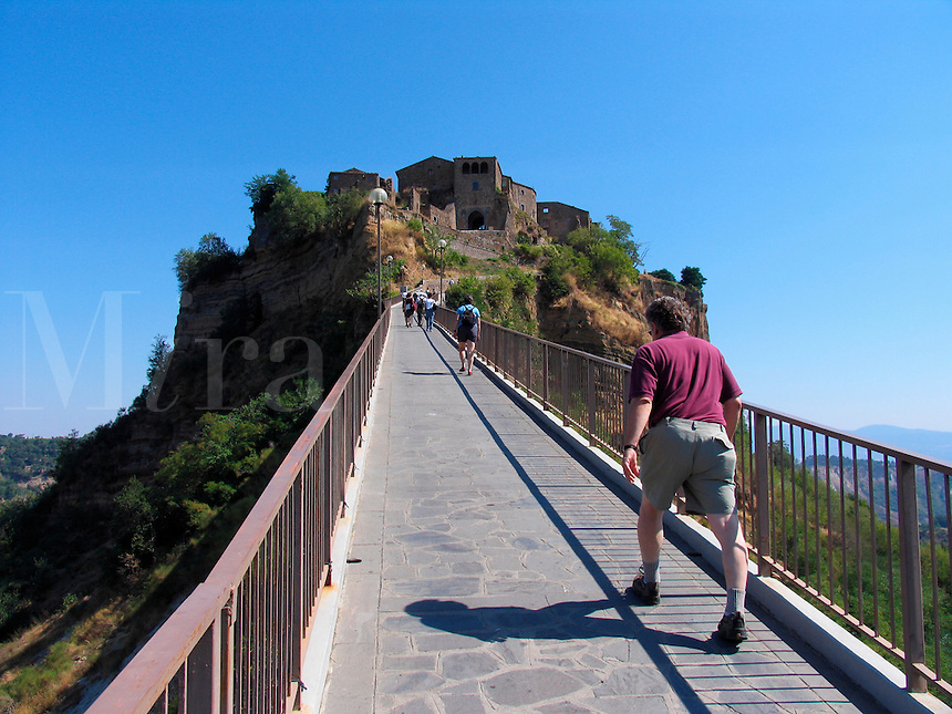 Tourists make the long climb up the bridge to Civita di Bagnoregio, Ital