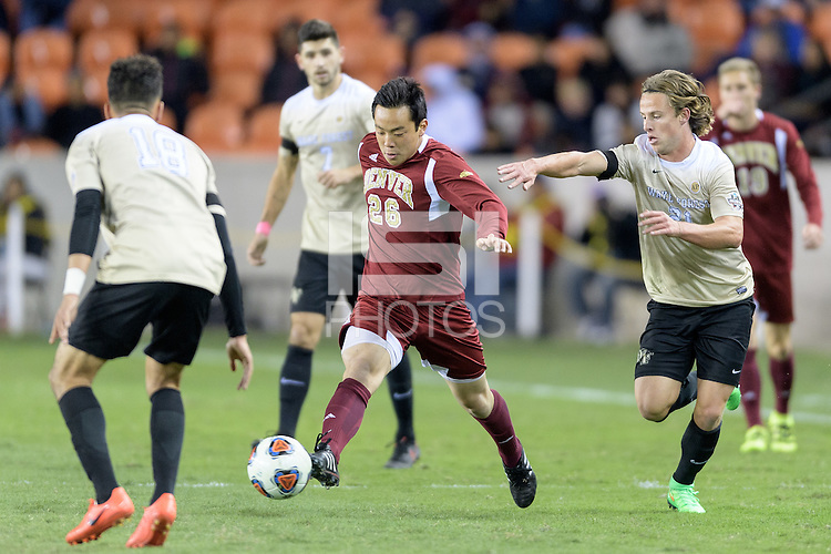 Houston, TX - Friday December 9, 2016: Kenny Akamatsu (26) of the Denver Pioneers dribble the ball around Hayden Partain (21) of the Wake Forest Demon Deacons at the NCAA Men's Soccer Semifinals at BBVA Compass Stadium in Houston Texas.