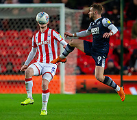 11th January 2020; Bet365 Stadium, Stoke, Staffordshire, England; English Championship Football, Stoke City versus Milwall FC; Tom Bradshaw of Millwall jumps to kick the ball - Strictly Editorial Use Only. No use with unauthorized audio, video, data, fixture lists, club/league logos or 'live' services. Online in-match use limited to 120 images, no video emulation. No use in betting, games or single club/league/player publications