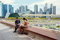 Two shop employees eat lunch beside a pond outside the shopping mall attached to the Marina Bay Sands resort.