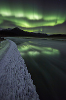 Northern lights reflect in the water of a river in Alaska's arctic Brooks Range.