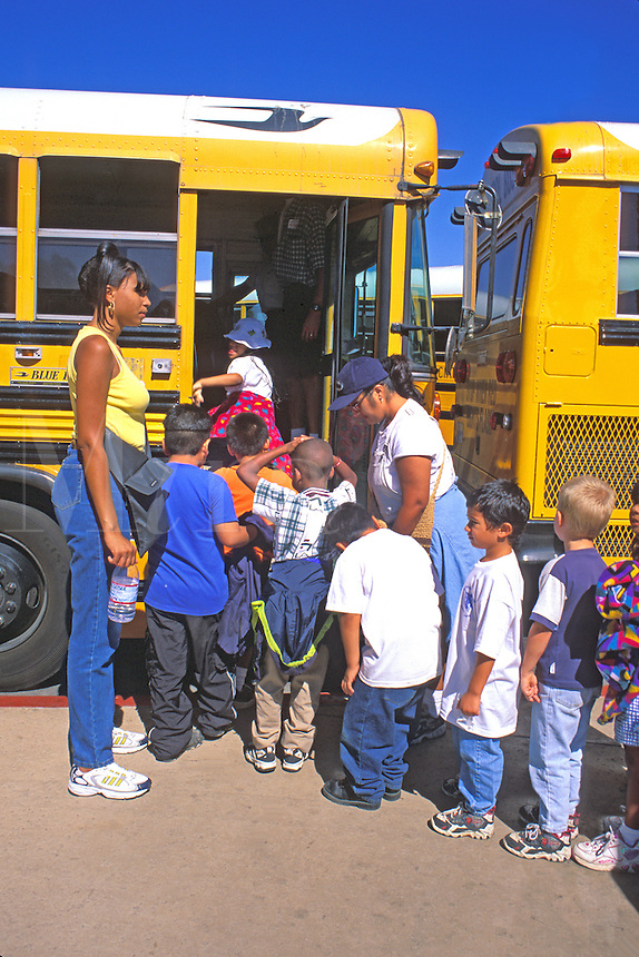 African American teacher supervises mixed ethnic elementary school children boarding school bus
