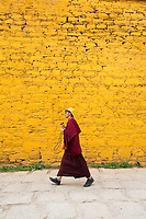 A monk walks through the narrow alleyways of Ganden monastery in Tibet. The monastery is one of the most important in the region and sits on top of a mountain near Lhasa at an altitude over approximately 4,300m.