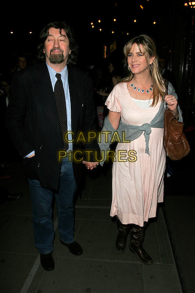 "TREVOR NUNN & IMOGEN STUBBS .""Gone With The Wind"" press night party, Waldorf Hotel, Aldwych, London, England..April 22nd, 2008.half length black suit jacket jeans denim holding hands married husband wife pink white polka dot dress gray gray wrap cardigan brown bag purse .CAP/AH.©Adam Houghton/Capital Pictures."