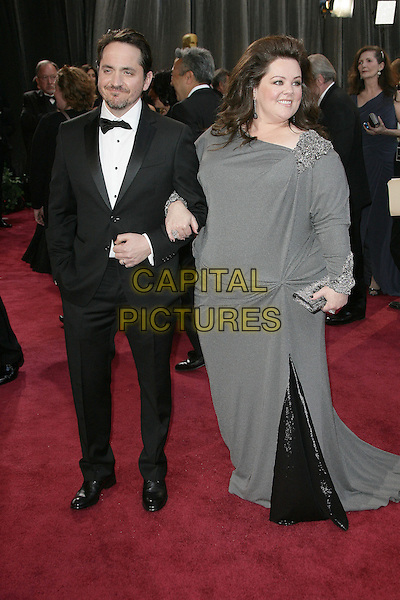 Ben Falcone, Melissa McCarthy.85th Annual Academy Awards held at the Dolby Theatre at Hollywood & Highland Center, Hollywood, California, USA..February 24th, 2013.oscars full length dress grey gray embellished jewel encrusted clutch bag tuxedo black white shirt married husband wife .CAP/ADM.©AdMedia/Capital Pictures.