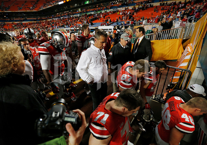 Ohio State Buckeyes head coach Urban Meyer and his team head to the locker room after losing the Discover Orange Bowl between Ohio State and Clemson at Sun Life Stadium in Miami Gardens, Florida, Saturday night, January 4, 2014.The Clemson Tigers defeated the Ohio State Buckeyes 40 - 35.(The Columbus Dispatch / Eamon Queeney)
