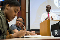"""Naomi Fedna, 23, of Randolph, MA, (left) takes notes as New York Assemblyman (79th District) and Vice Chair of the Democratic National Committee Michael Blake speaks to a live audience during a session of Resistance School in the Starr Auditorium in the Belfer Building of Harvard University's John F. Kennedy School of Government, on Thurs., April 27, 2017. Blake's lecture was titled """"How to sustain the resistance long term."""" The lecture, which was the fourth such session and the final in what the group calls the """"first semester"""" of Resistance School, was also streamed live on the internet. Resistance School was started by progressive graduate students at Harvard after the Nov. 8, 2016, election of President Donald Trump. Resistance School describes itself as a """"practical training program that will sharpen the tools [needed] to fight back at the federal, state, and local levels."""" The live lectures are streamed and archived online alongside other information on the Resistance School website. During the lectures, teams of volunteers engage with followers on social media, including Facebook and twitter, sharing soundbytes, quotations, and supplementary materials as the lectures happen."""