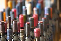 Many bottles and bottle necks in preparation for a large winetasting.