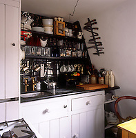 A kitchenette area with a sink set into a white painted unit with kitchenware arranged on black shelves above.